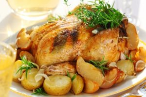 A whole roasted chicken with potatoes, herbs and spices